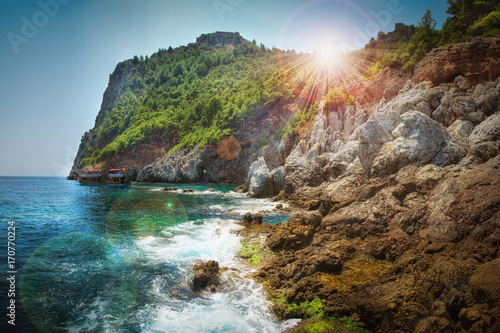 Fotobehang Tropical strand Mountains and sea scenery with blue sky and bright sun rays over mount, Greece.