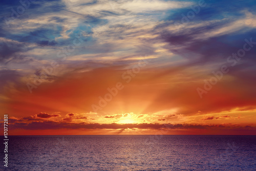 Foto op Aluminium Aubergine Beautiful colorful sunset at the sea with dramatic clouds and sun shining. Beauty world natural outdoors travel background