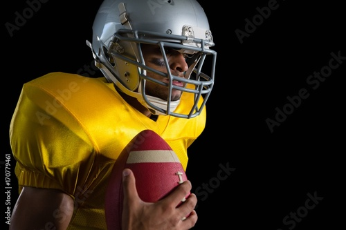 Fotobehang Voetbal American football player holding a ball