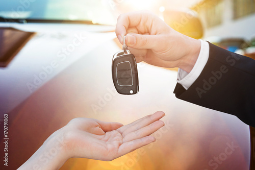Salesman Handing Key To Woman By New Car