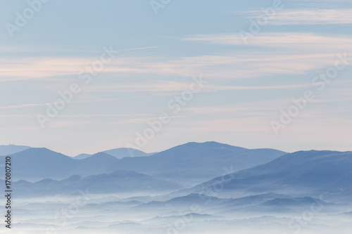 A view from above of a valley filled by a sea of fog, with various layers of emerging hills and mountains with different shades of blue - 170807210
