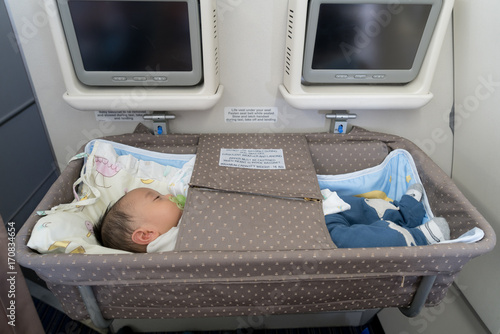Asian adorable baby boy sleeping In special bassinet on airplane. Poster