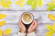Woman hands holding morning cup of coffee on vintage wooden table decorated autumn yellow leaves top view. Cozy fall breakfast. Flat lay.