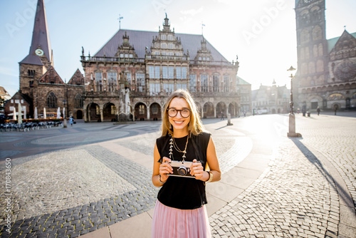Portrait of a young woman tourist standing on the central square of Bremen city, Germany