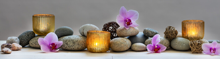 concept of wellbeing with pebbles, orchids and candles, panoramic © STUDIO GRAND WEB