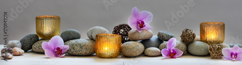 Foto op Plexiglas Spa concept of wellbeing with pebbles, orchids and candles, panoramic