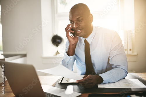 Smiling businessman reading paperwork over the phone and working