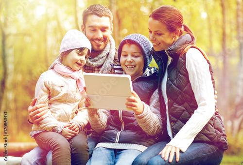family sitting on bench with tablet pc at camp