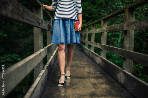 Woman with book on bridge in forest
