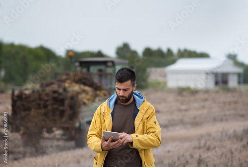 Farmer holding tablet with tractor behind Poster
