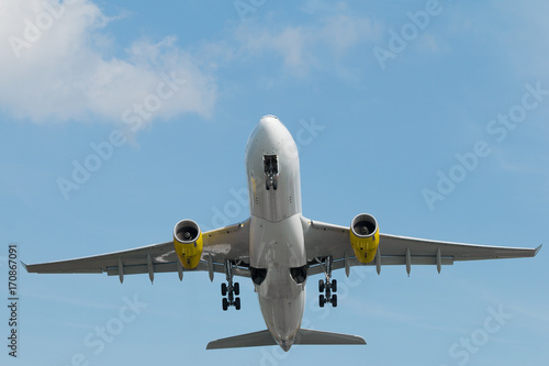Low angle view of airplane flying up to the blue sky. Poster