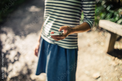 Young woman using smart phone in the forest