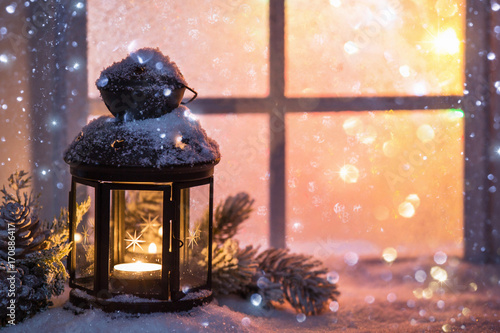 Winter decoration with a candlestick near the snow-covered window плакат