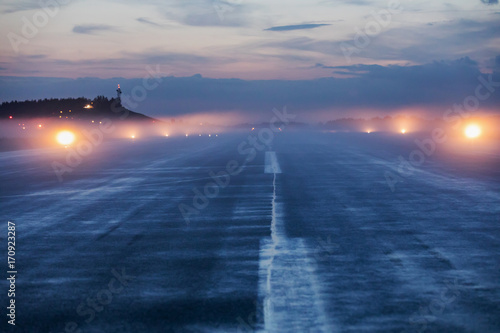 Empty runway at airport during a foggy evening Poster