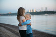 brother hugging sister on the river Bank
