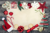 Christmas background border with bauble decorations, holly, mistletoe, fir, mince pies and gingerbread biscuits on parchment paper on rustic wood background. - 170937013