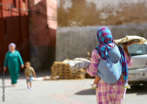 Fotobehang Marokko Moroccan woman with a child behind her, sells bread on the streets of the city