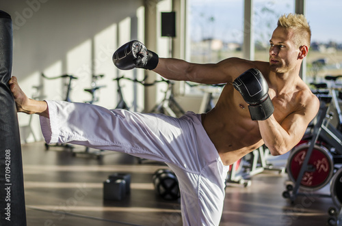 Shirtless handsome muscular young man in gym doing kick against punching bag, we Poster