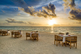 Tropical restaurant on the sandy beach. Landscape of beautiful sunset in Maldives island with colorful sky and dramatic clouds over wavy sea. - 170947007