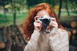 redhead girl holding camera in autumn park
