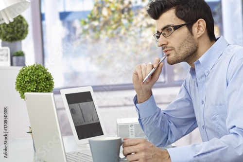 Young man thinking at desk