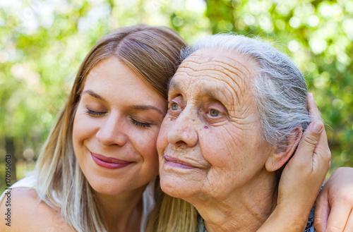 Leinwandbild Motiv Hugging grandma in the park