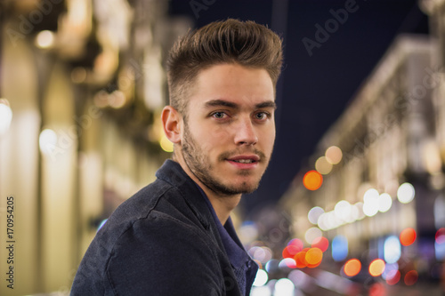 Wall mural Attractive young man portrait at night with city lights behind him in Turin, Italy