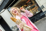 Cheerful elegant woman holding baguette in rue Lepic in Montmartre, Paris, France. Caucasian happy blonde woman with traditional French bread outdoor. Bakery on blurred background.
