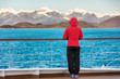 Alaska cruise travel tourist woman watching nature landscape from boat standing in cold morning weather with winter jacket in inside passage, Glacier Bay, USA.
