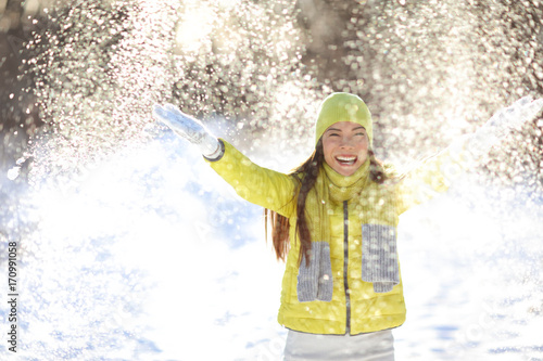 Fotobehang Hoogte schaal Happy winter fun woman playing throwing snow with arms up open in freedom enjoying the cold season