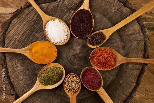 Poster Assortment of indian spices and herbs in wooden spoon