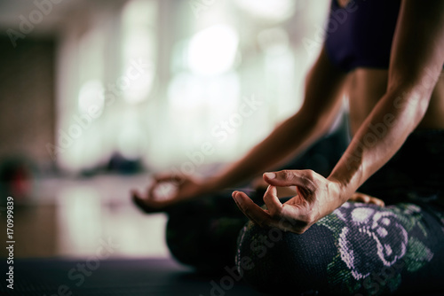Fotobehang School de yoga Close up view of young woman meditates while practicing yoga in a studio. Freedom concept. Calmness and relax,