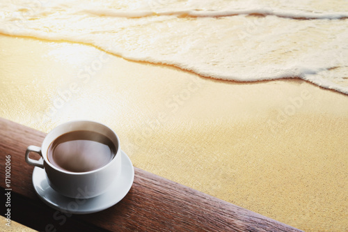 Papiers peints Cafe Cup of hot coffee drinks on wood table, on the beach in sunrise