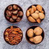 Whole almonds,whole walnuts ,whole hazelnut and pecan nuts in wooden bowl setup with stone background.  Selective focus depth of field. - 171007009