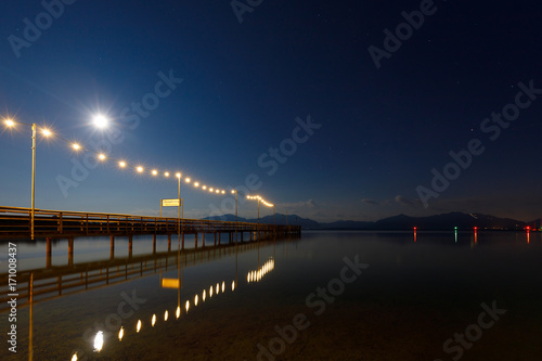 Jetty at night with full moon at Lake Chiemsee, Seebruck, Bavaria, Germany, (Translation sign: Steamer jetty, Departure to Islands)