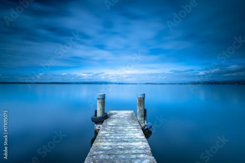 Pochmurny. Drewniane molo. Jezioro na horyzoncie. Długa ekspozycja.