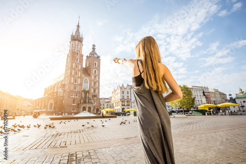 Portrait of a young stylish woman tourist in front of the famous St. Mary's Basilica on the Market square during the sunrise in Krakow, Poland