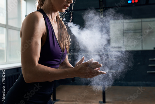 Wall mural Side view closeup of young  woman covering hands with talk in dark gym preparing for heavy weightlifting