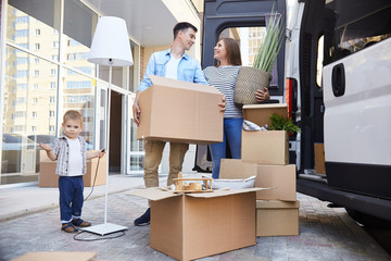 Portrait of happy young family holding cardboard boxes standing next to moving van and smiling
