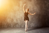 Young beautiful woman prima theater in a black pack, white pantyhose, white pointe shoes beautifully dances Russian ballet in a black dance studio...