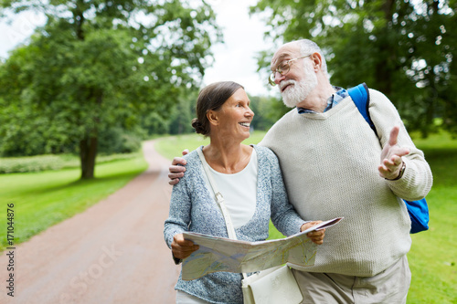 Cheerful mature travelers moving down country road