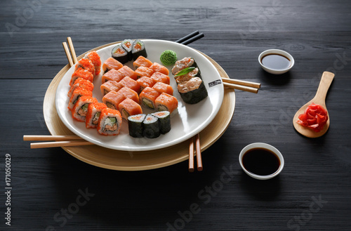 Set of salmon sushi and rolls on black background, top view