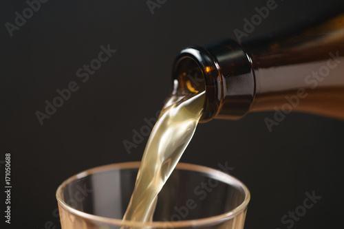 wheat beer pouring in glass on dark background Poster