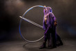 Fairy-tale character assassin in a purple cloak with a hood with two large cyr wheel hoops