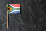 A South African flag toothpick on a black slate background. - 171054207