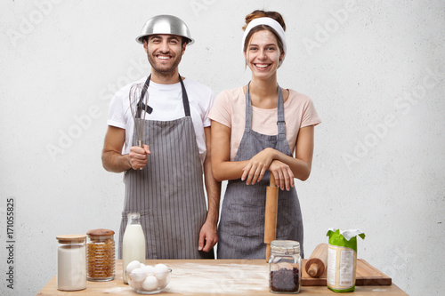 Family couple cooking at home, baking cake, having happy expressions. Pretty female with dirty face holding rolling pin in hands standing near her attractive husband who has fun posing with whisk