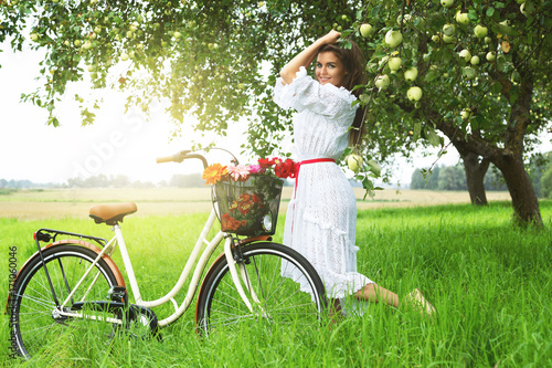 Woman on the bicycle is picking fresh apples from the tree in the village garden