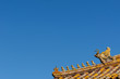 Detail of sculptures in the rooftop of a building at the Forbidden City in Beijing, China, against a clear blue sky