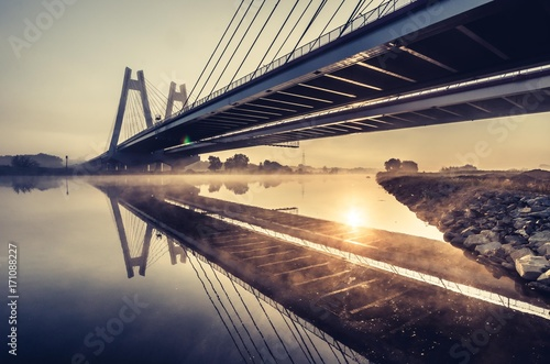 Fototapeta Cable stayed bridge, Krakow, Poland, in the morning fog over Vistula river