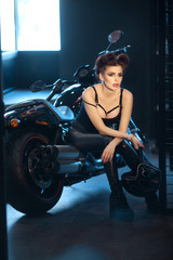 beautiful young girl in black clothes sitting on a motorcycle